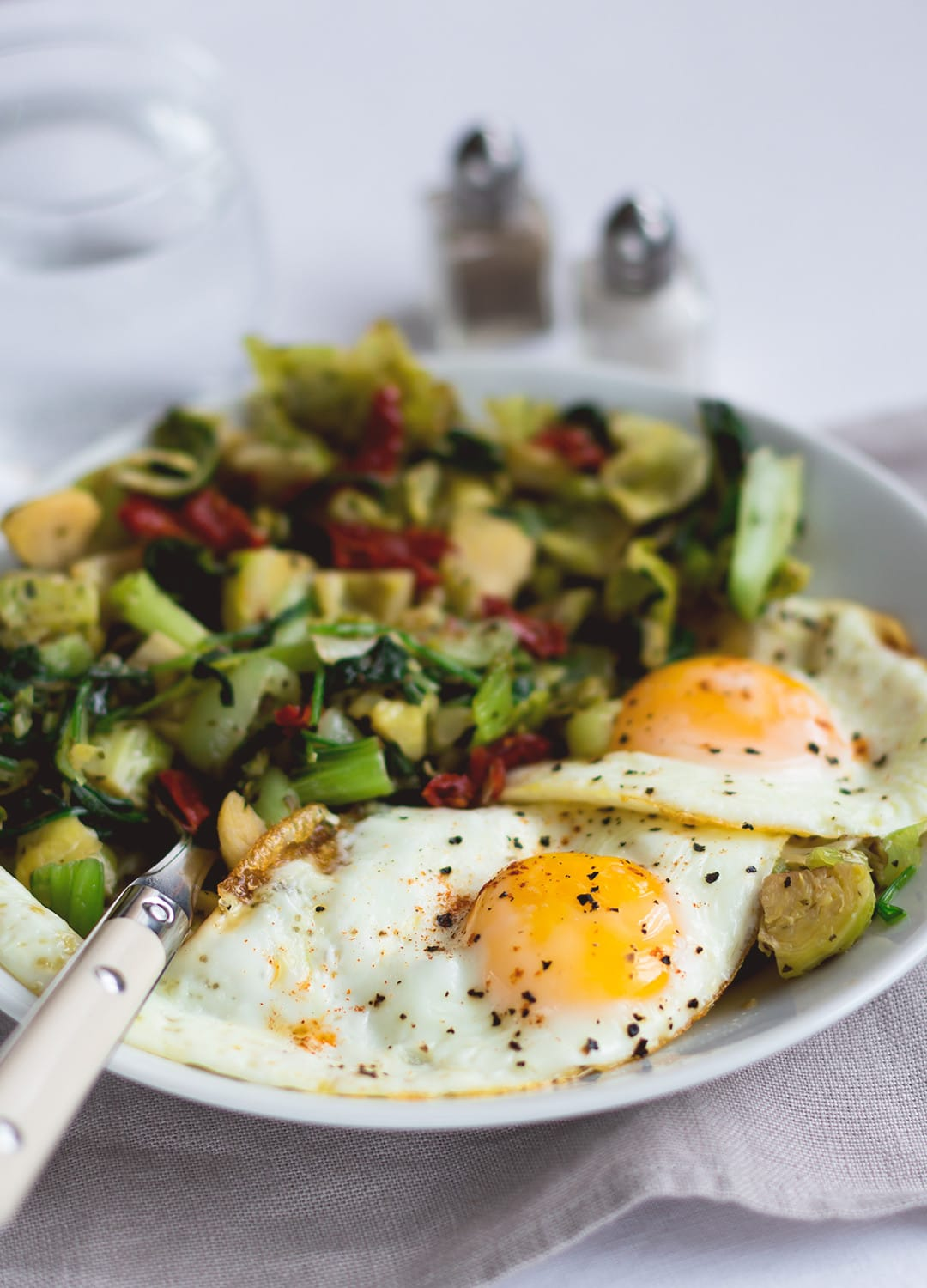 Sauteed pak Choy and Brussels Sprouts with Eggs Sunny Side Up - this is the ultimate savory breafast for a morning when you have a little bit more time to spend in the kitchen. It's probably my most favorite savory breakfast, because it includes eggs and all things green (I also sneaked in some baby spinach for even more of a healthy kick!) . I love to pair this with avocado on toast. | thehealthfulideas.com