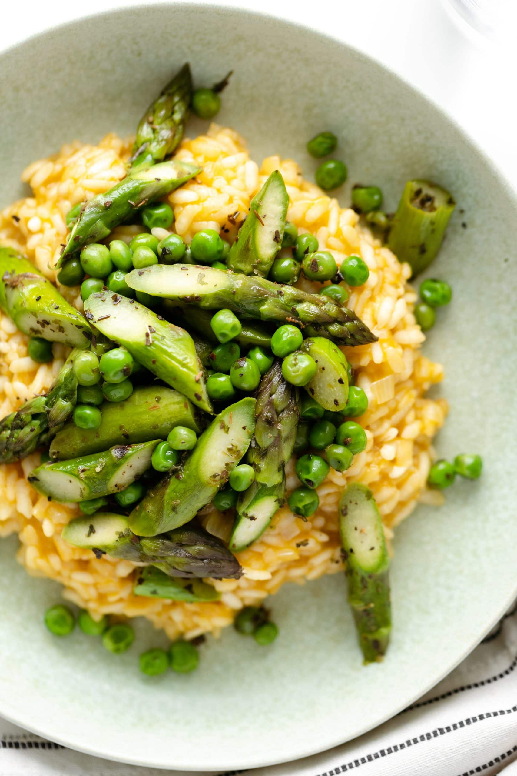 A shot of arborio risotto from above served with asparagus and peas