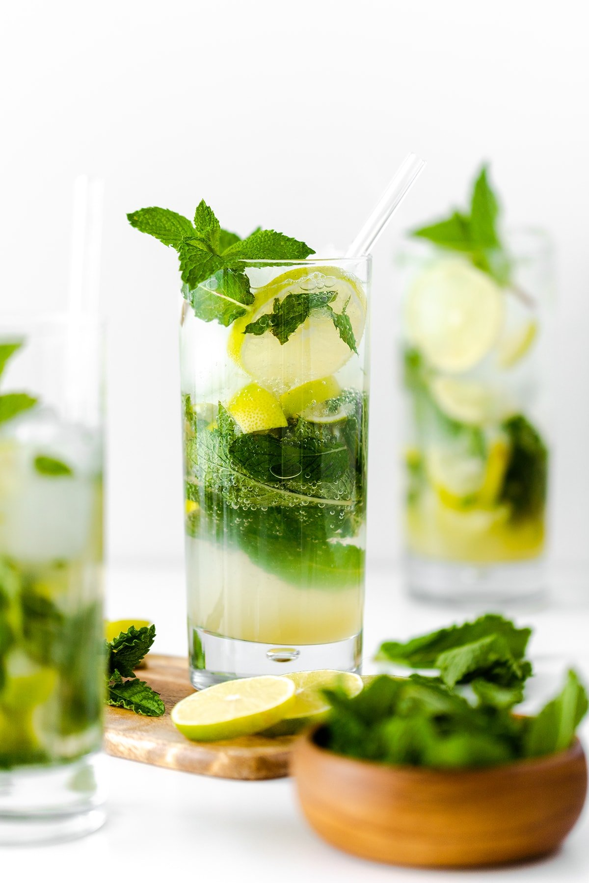 Head on shot of mojitos with mint leaves. Two mojitos are out of focus with one is in focus.