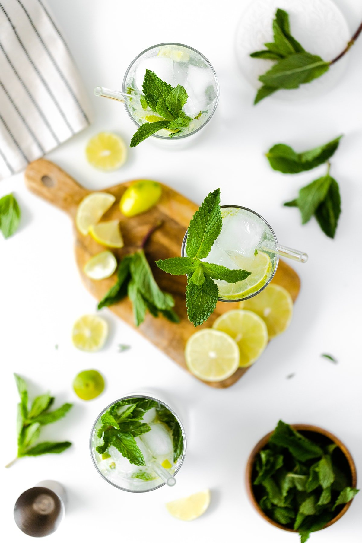 A wide overhead photo of mojitos on a white background with wooden board and a washcloth
