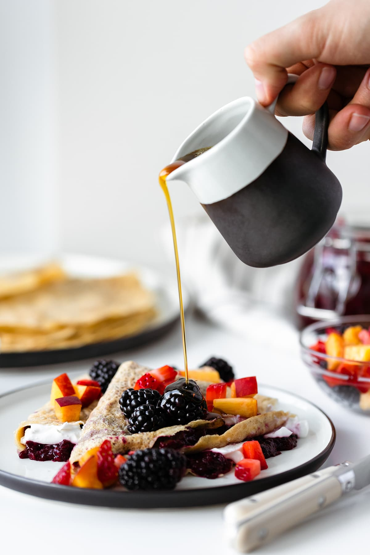 Maple syrup being poured over gluten-free crepes with Lavender Blackberry Jam