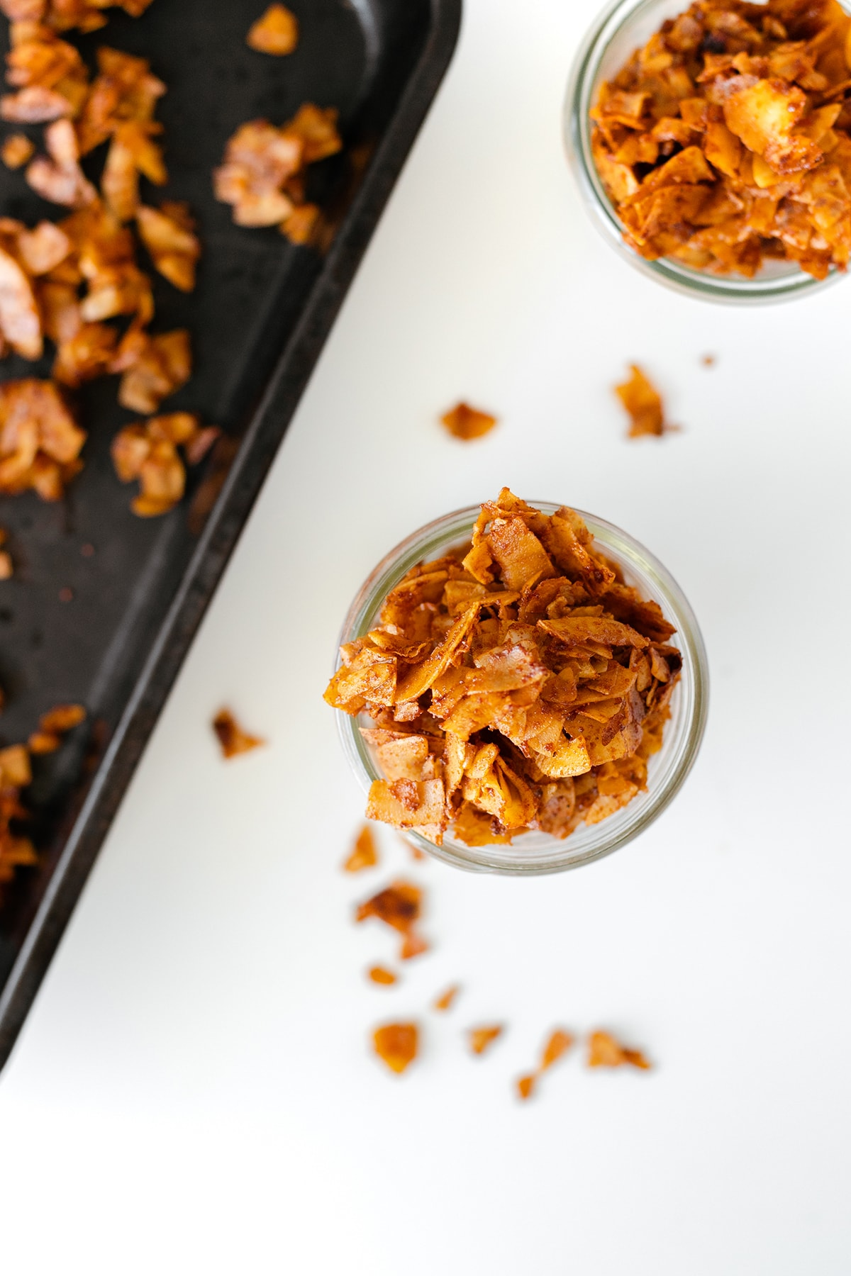 Overhead shot of vegan coconut bacon in a glass jar and on a baking pan