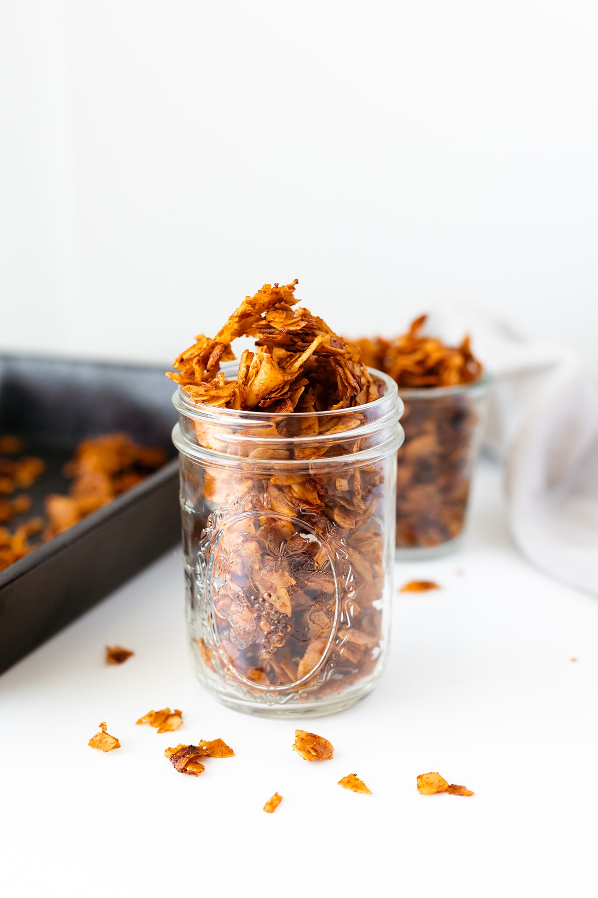 Vegan coconut bacon in a glass jar with a baking sheet in the background