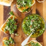 Sliced toasted baguette on a wooden cutting board, with chimichurri sauce in a glass bowl