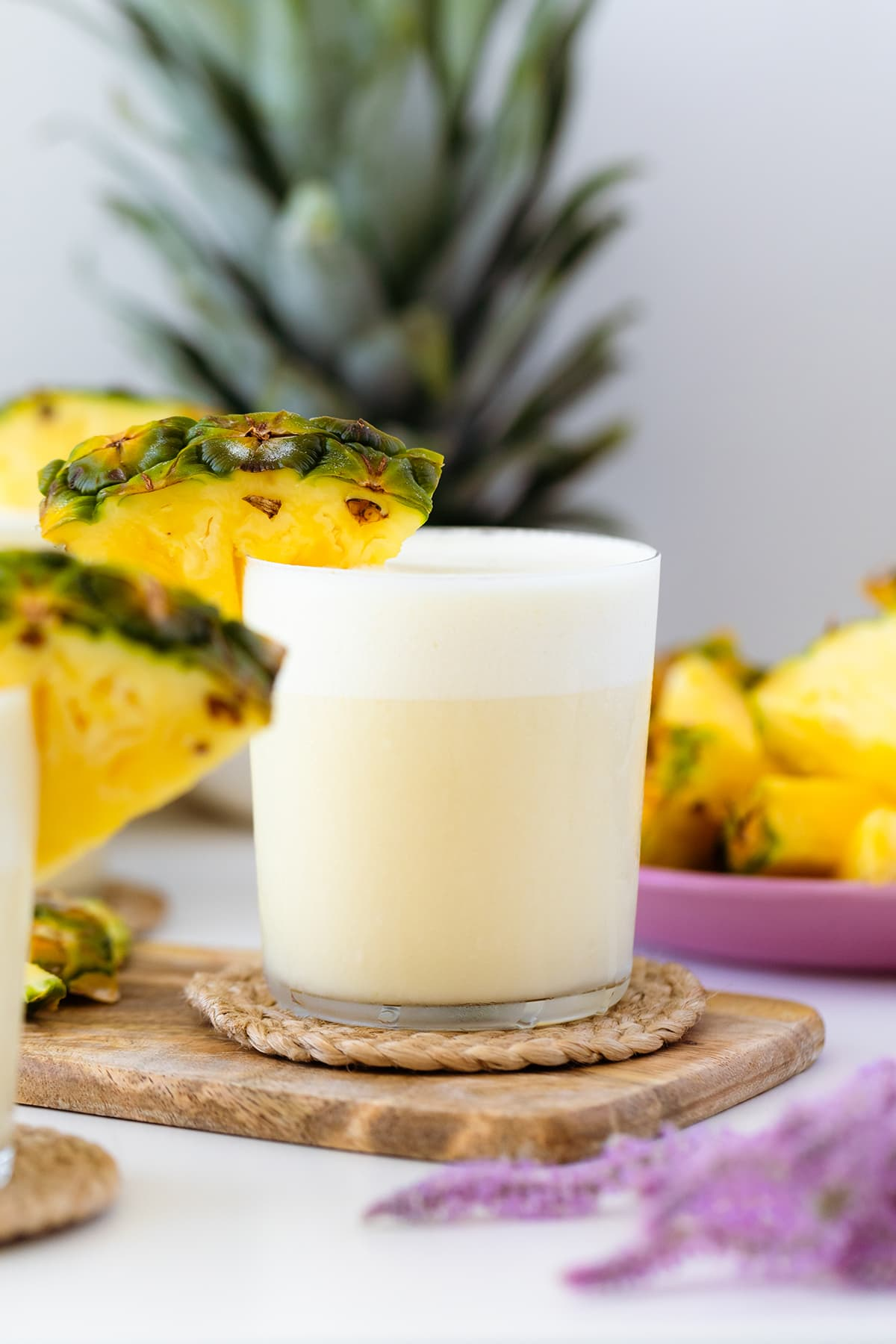 A head on shot of Skinny Pina Colada cocktail decorated with pineapple on a while table