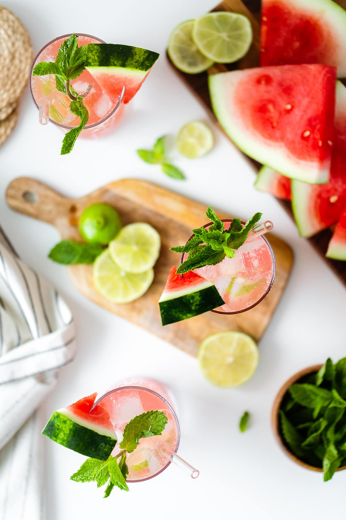 Watermelon Coconut Rum Cooler overhead shot, one drink on a small wooden cutting board, the other two on white table with watermelon slices on the right