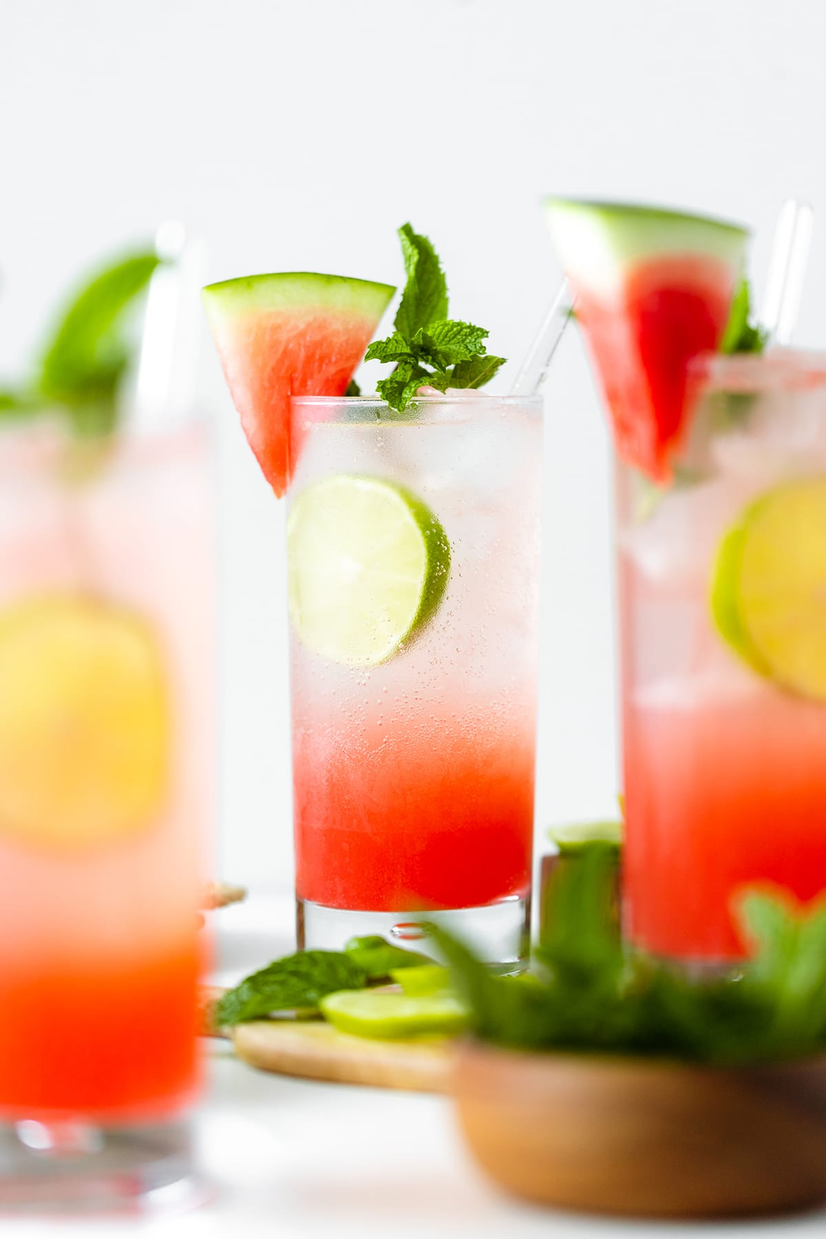 Watermelon Coconut Rum Cooler - three glasses in shot, head on, decorated with mint, lime, and watermelon slice