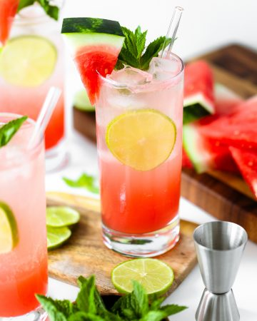 Watermelon Coconut Rum Cooler - three glasses in shot, head on, decorated with mint, lime, and watermelon slice. White background