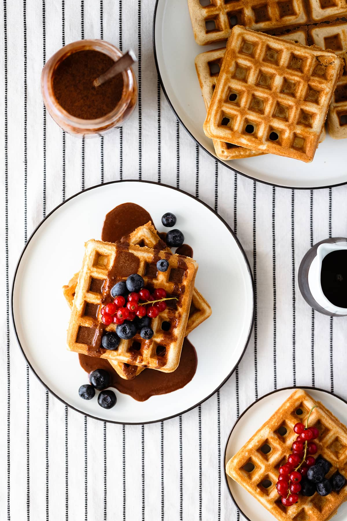 Basic Gluten-free Waffles with Tahini Chocolate Sauce and berries on a white plate and a white table cloth with black stripes