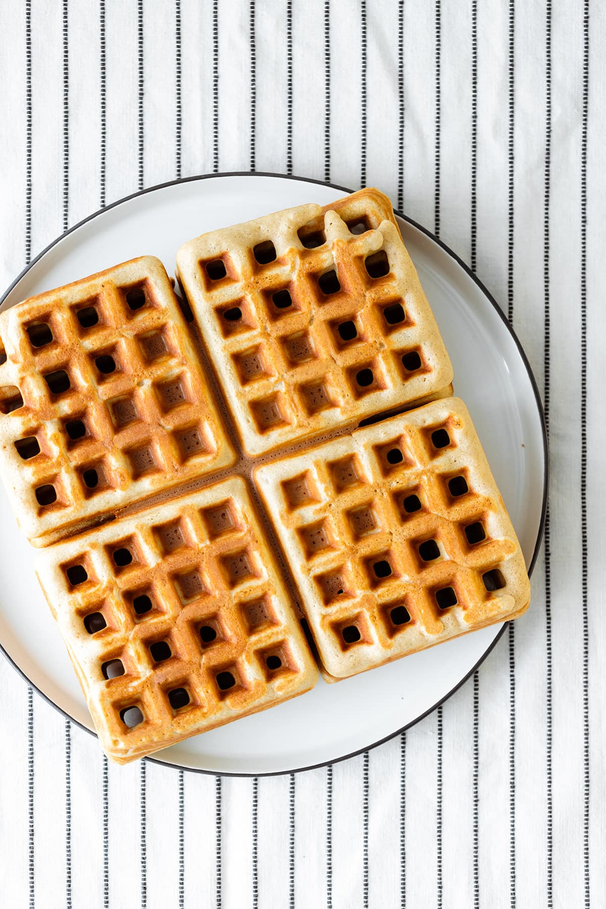 4 Basic Gluten-free Waffles on a white plate and a white table cloth with black stripes