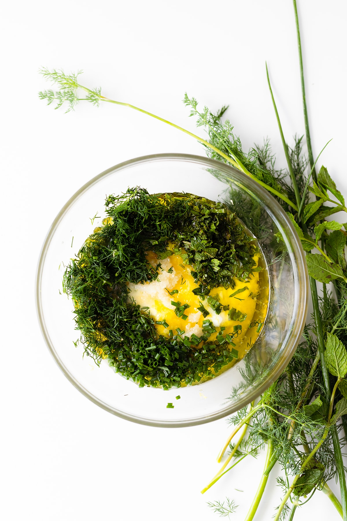 Fresh herbs, yogurt, olive oil, and lemon juice in a glass bowl on white background. Overhead shot