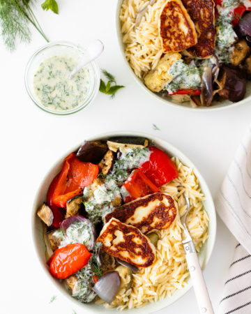 Halloumi Orzo Bowl with Roasted Vegetables and Yogurt Dill Sauce on two plates on a white table decorated with fresh herbs and a striped cloth on the right side of the frame. Overhead shot