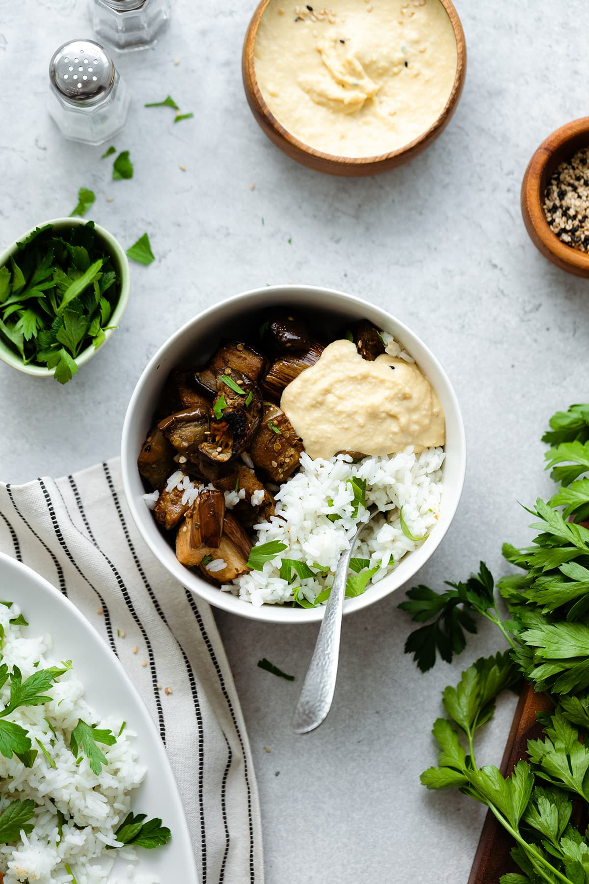 Spicy Garlic Miso Roasted Eggplant in a small bowl with white rice, parsley, and hummus. Grey background