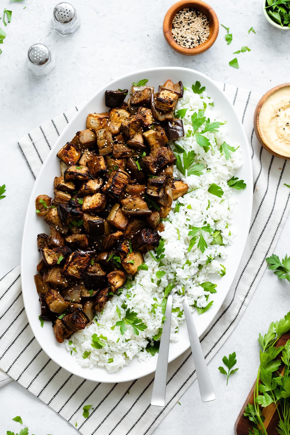 Spicy Garlic Miso Roasted Eggplant with white basmati rice and a sprinkle of parsley on a big oval plate