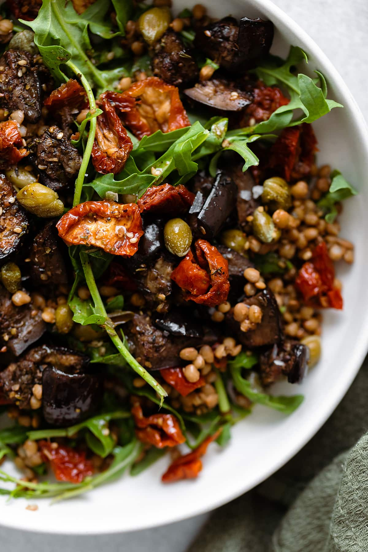 Za'atar Roasted Eggplant Lentil Salad with Sundried Tomatoes in white bowl close up