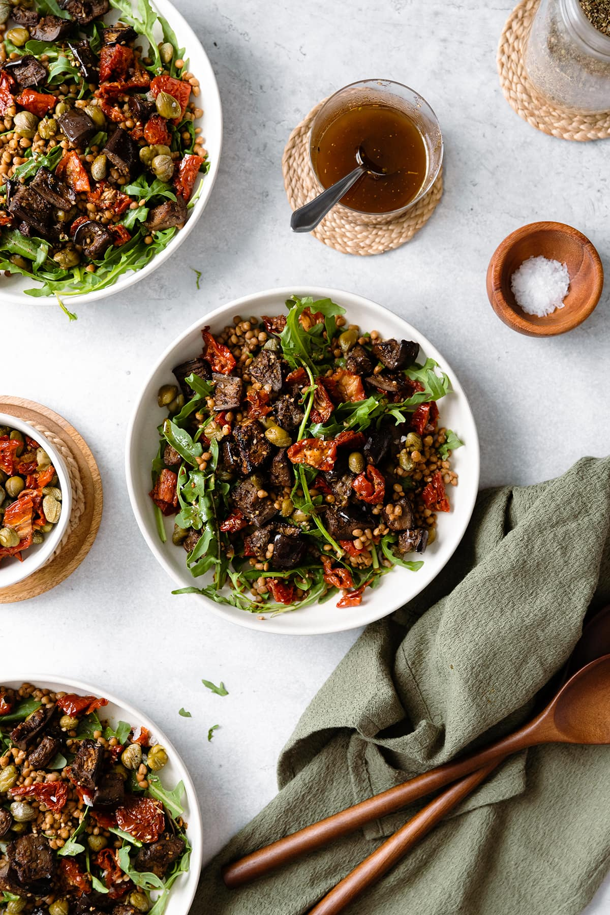 Za'atar Roasted Eggplant Lentil Salad with Sundried Tomatoes in white bowl on a grey background