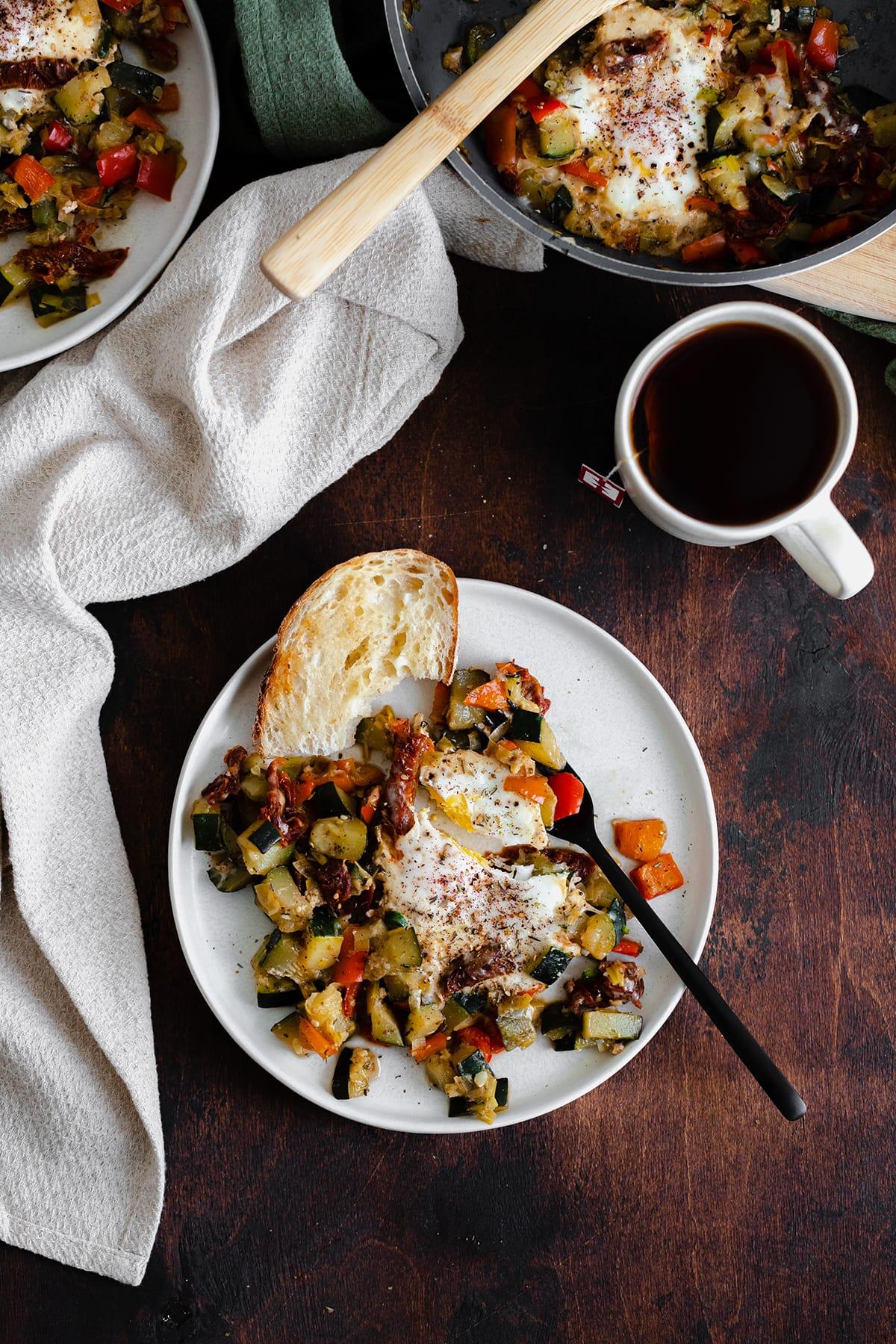 A photo of Bell Pepper and Zucchini Breakfast Skillet with Za'atar on a white plate and a wooden table