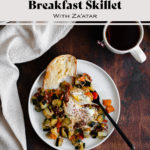 An overhead photo of Bell Pepper and Zucchini Breakfast Skillet with Za'atar on a white plate with text overlay (the title)