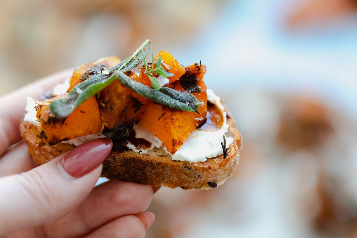 A photo of a hand holding Butternut Squash Crostini with Goat Cheese and Fig Balsamic Glaze