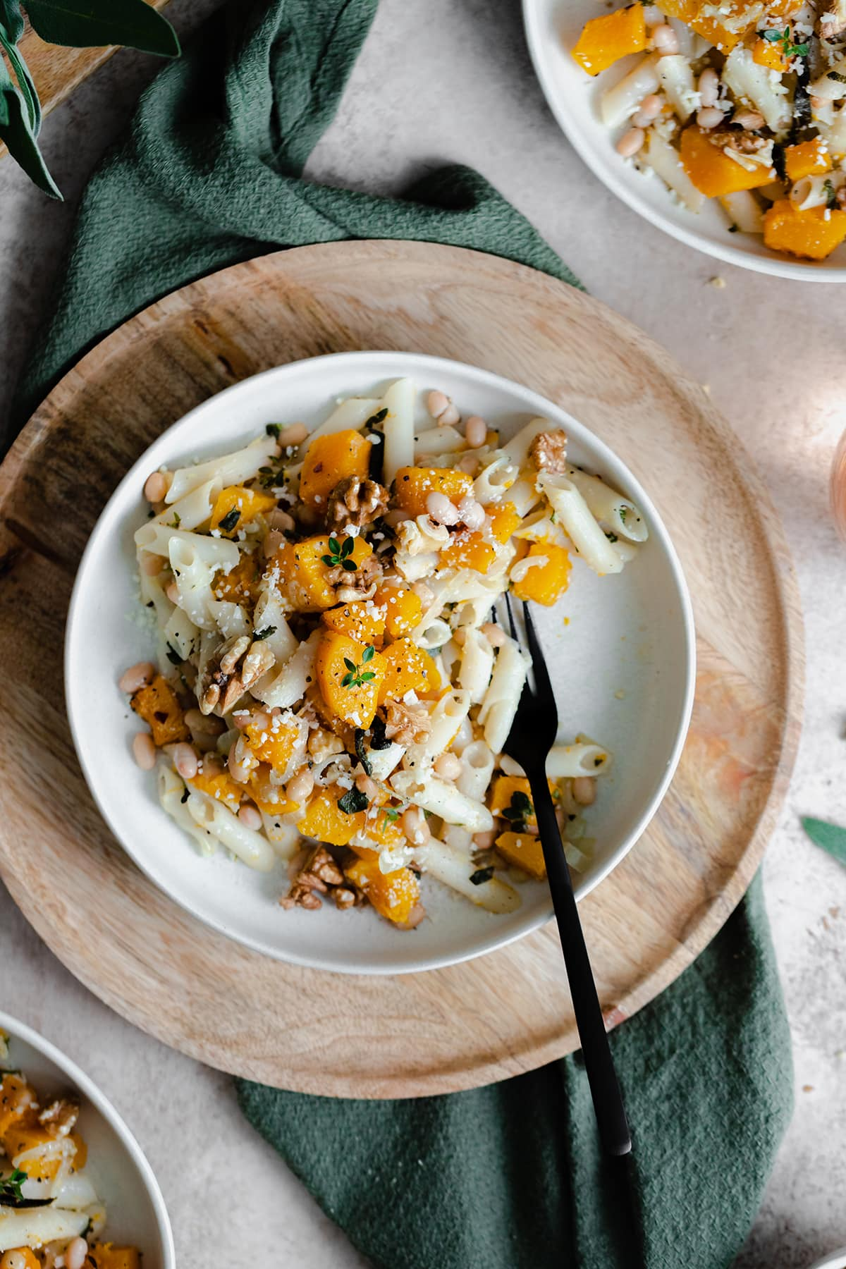 A vertical overhead shot of Butternut Squash Penne with Sage and Toasted Walnuts on a white plate