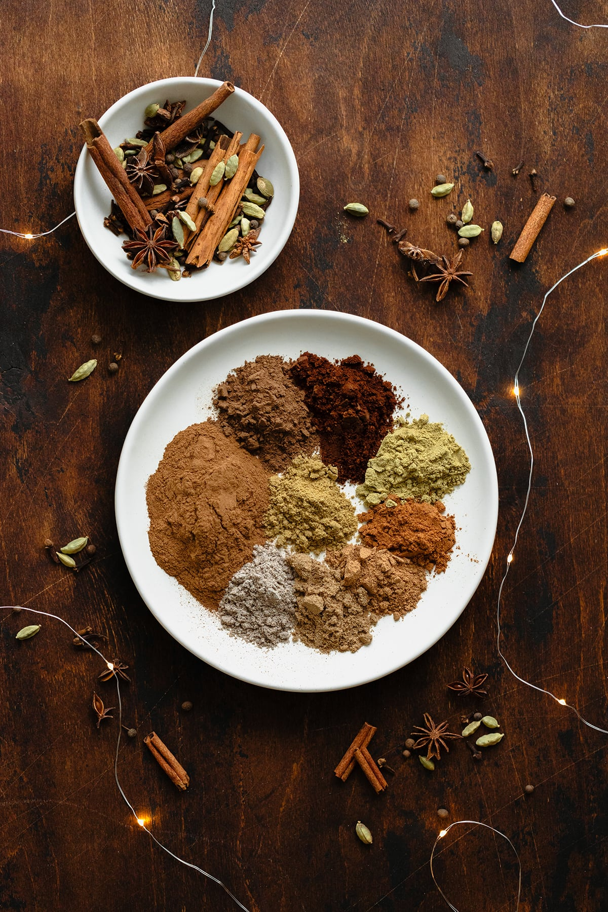 A photo of all the spices used in the Christmas Spice Blend on a white plate. On a dark wooden background and fairy lights.