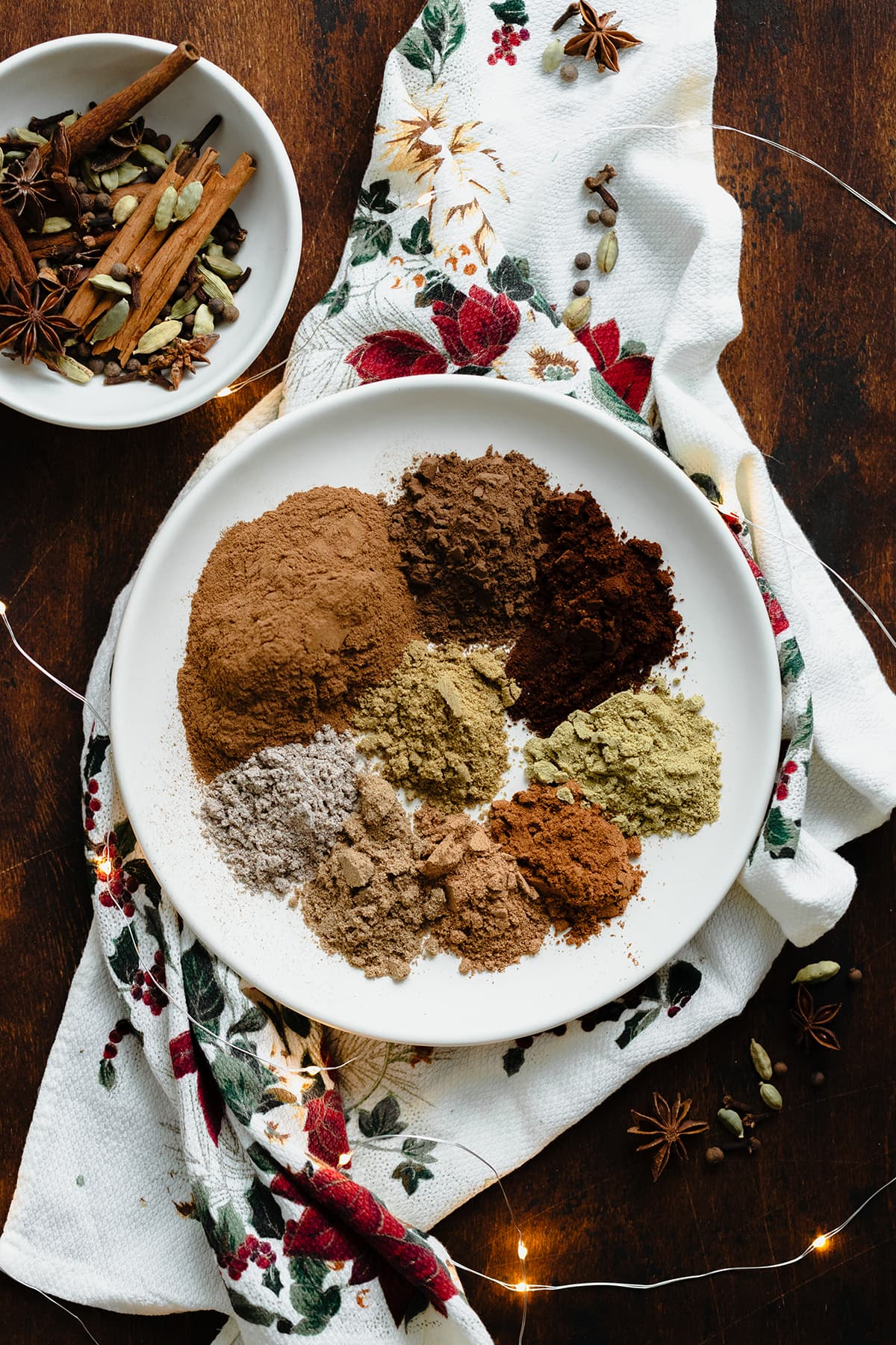 A photo of all the spices used in the Christmas Spice Blend on a white plate. On a dark wooden background.