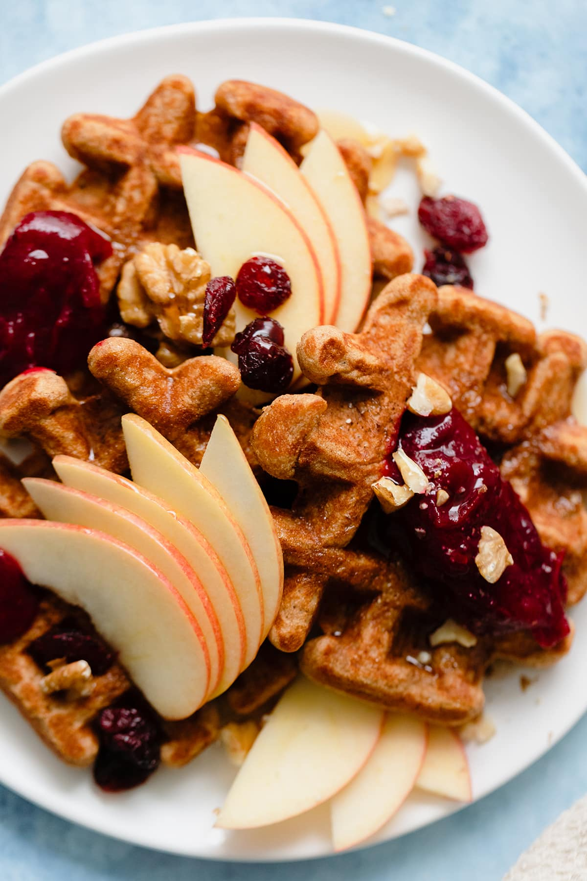 An overhead photo fo Gluten-Free Apple Butter Waffles with apples, cranberries, and walnuts on blue background.