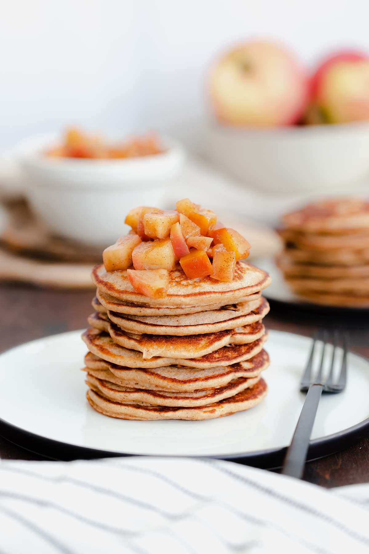 A straight on photo of Chocolate Chip Apple Cider Pancakes with Stewed Apples on a white plate and dark wooden background.