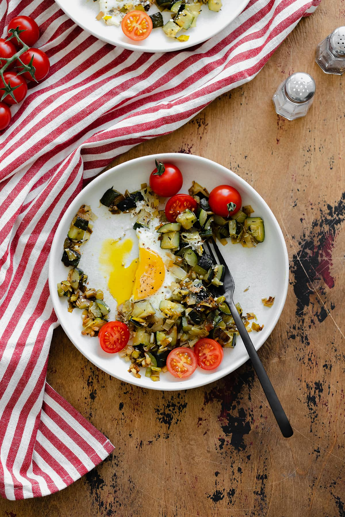An overhead shot of Leek and Zucchini Egg Skillet on a red and white striped kitchen towel and wooden table