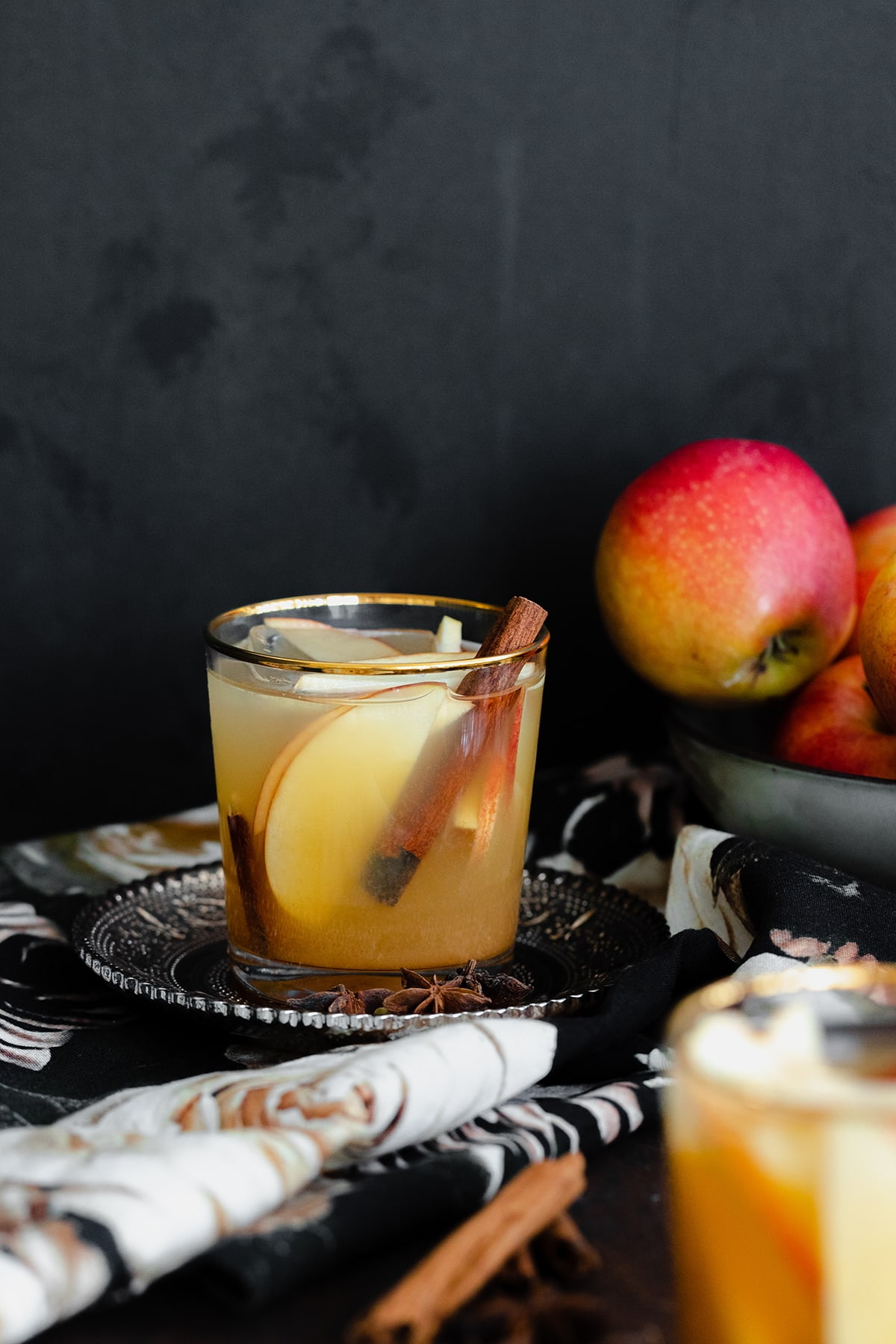 A straight on photo of Spiced Rum Apple Cider Cocktail in a short glass with a golden rim