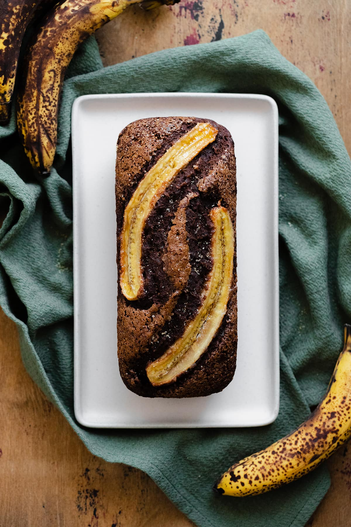 A photo of Caramelized Chocolate Banana Bread on a beige plate, green kitchen towel, and light wooden table.