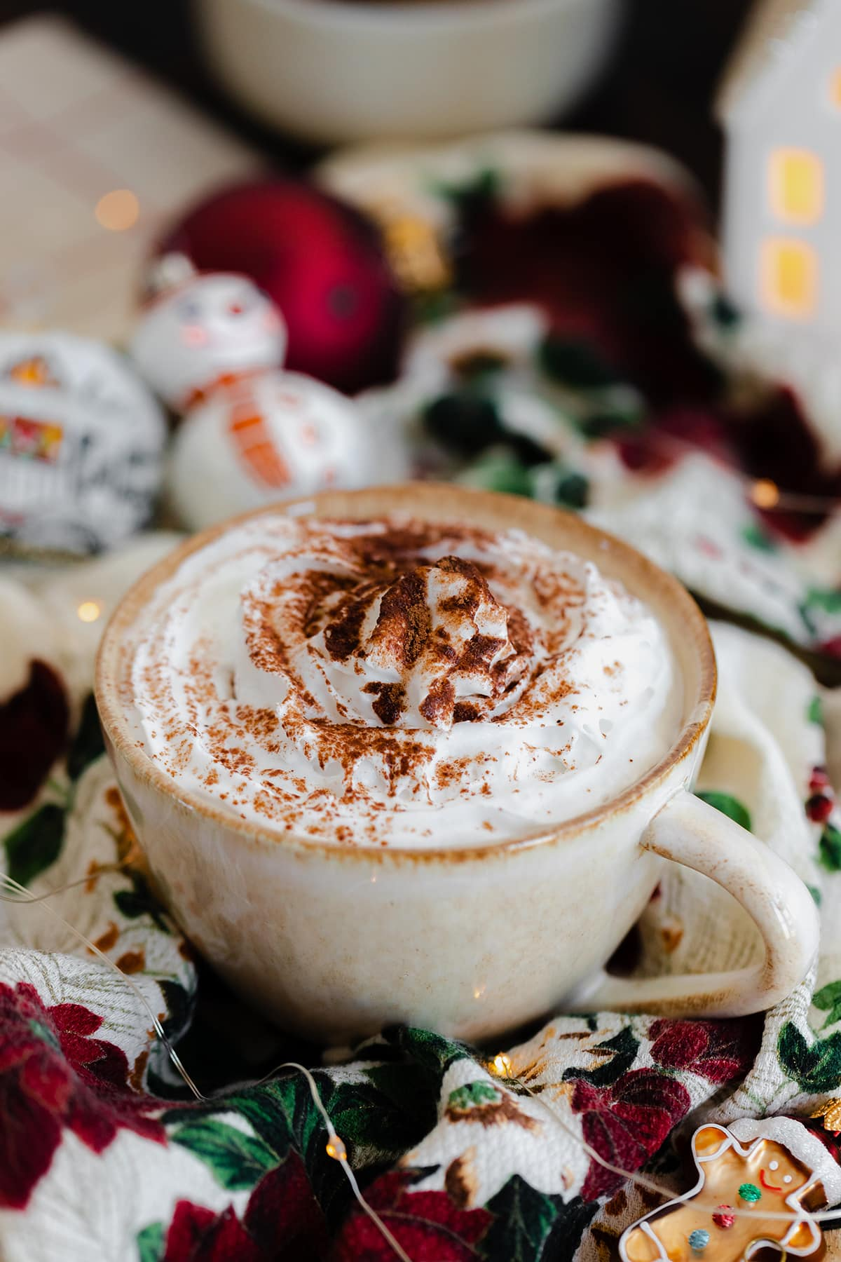 A shot of Christmas Spiced Hot Chocolate with whipped cream, dusted with gingerbread spice in a beige cup.