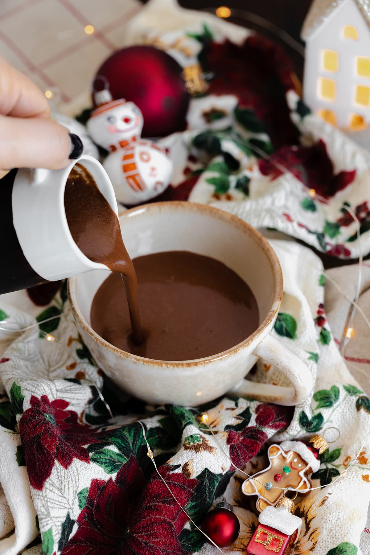 A shot of the hot chocolate being poured into a cup on a Christmas themed tablecloth.