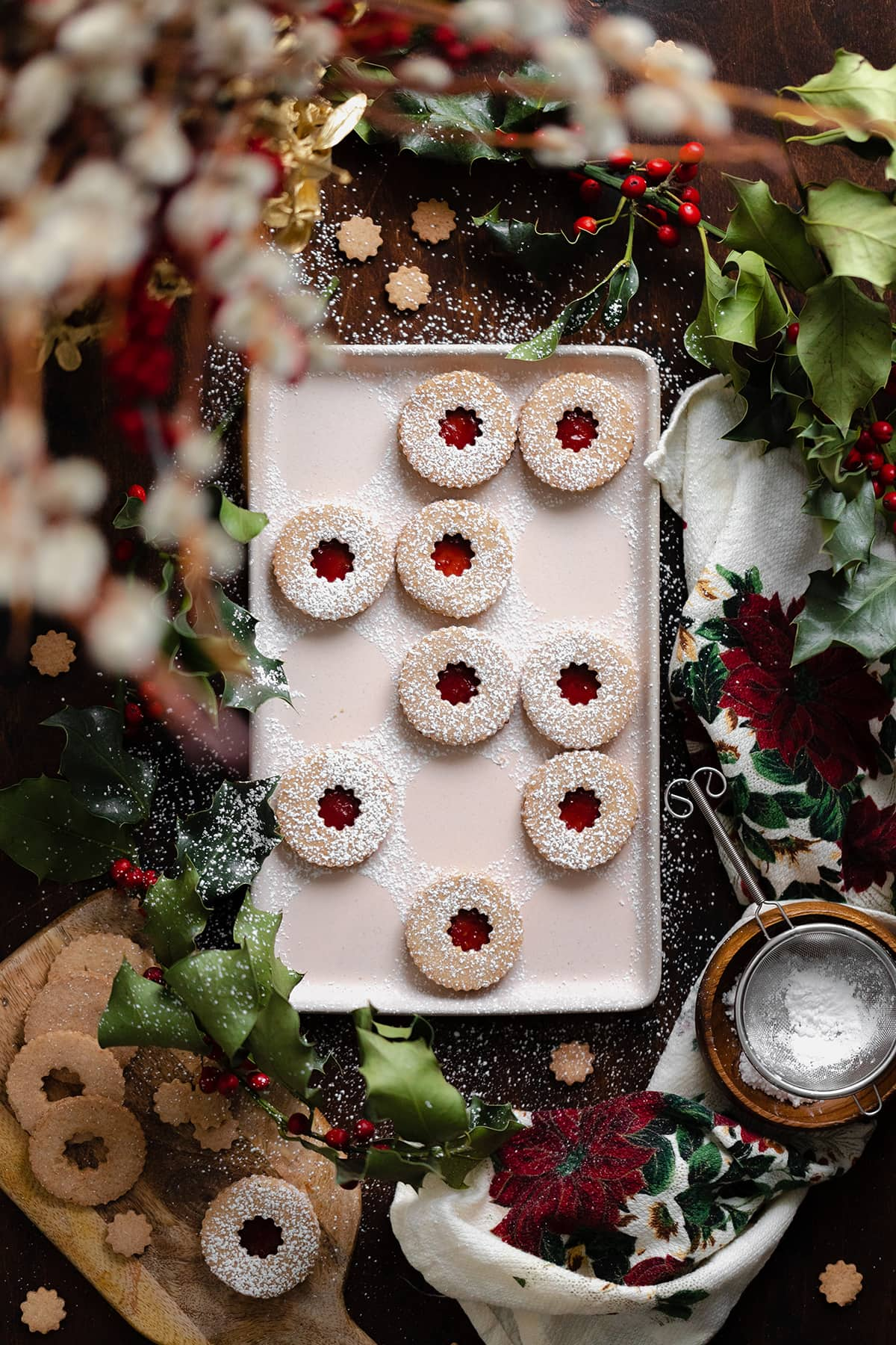 Gluten-Free Linzer Cookies with raspberry jam and a dusting of powdered sugar on a beige plate. Decorated with Christmas decorations all around the plate