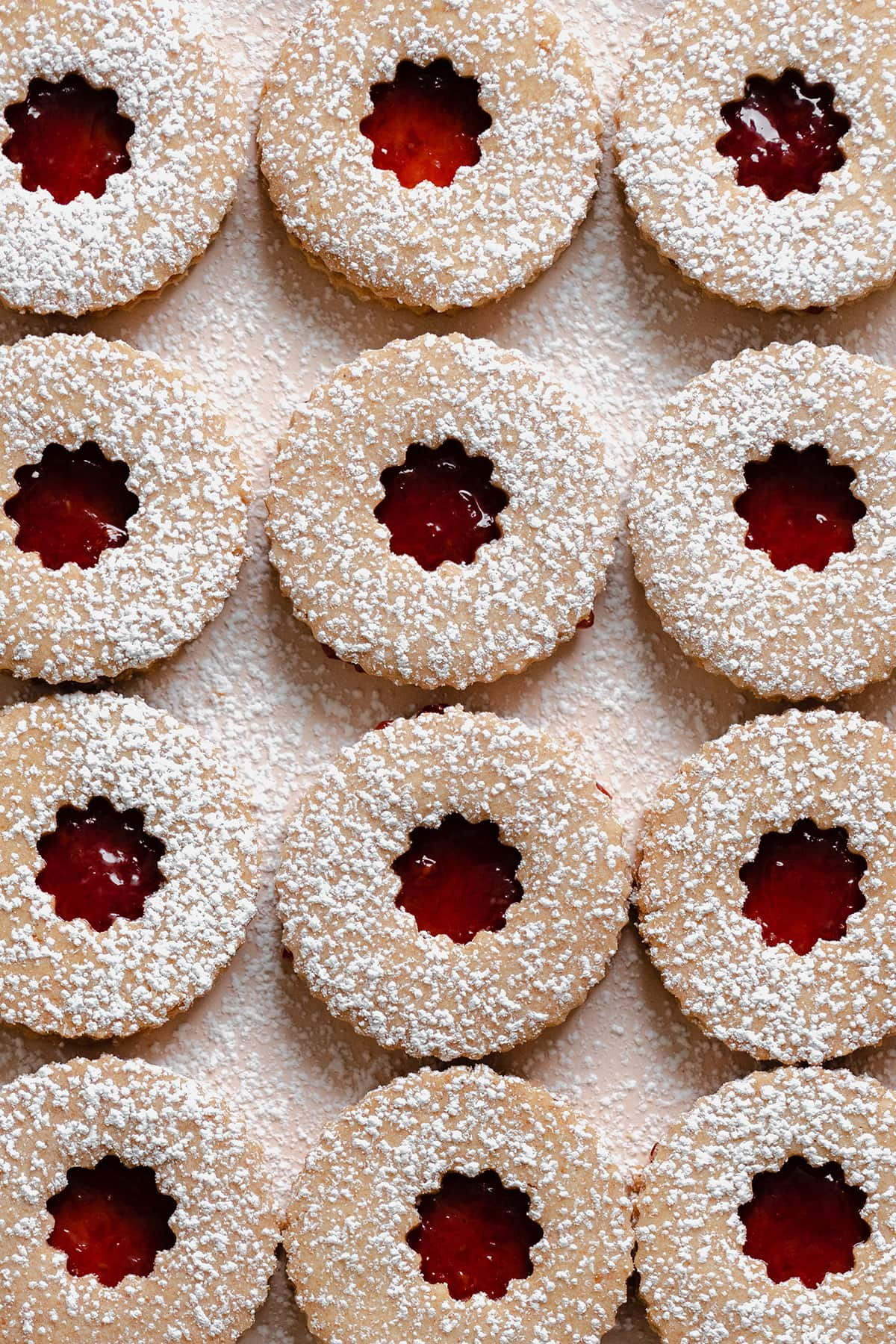 A close up image of Linzer Cookies with raspberry jam and a dusting of powdered sugar on a beige plate.