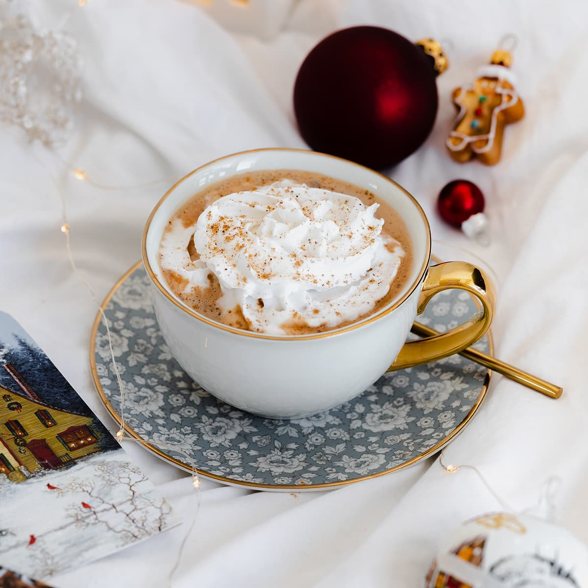 Vegan Eggnog Mocha with whipped cream and a sprinkle of nutmeg in a white mug on white bedsheets.