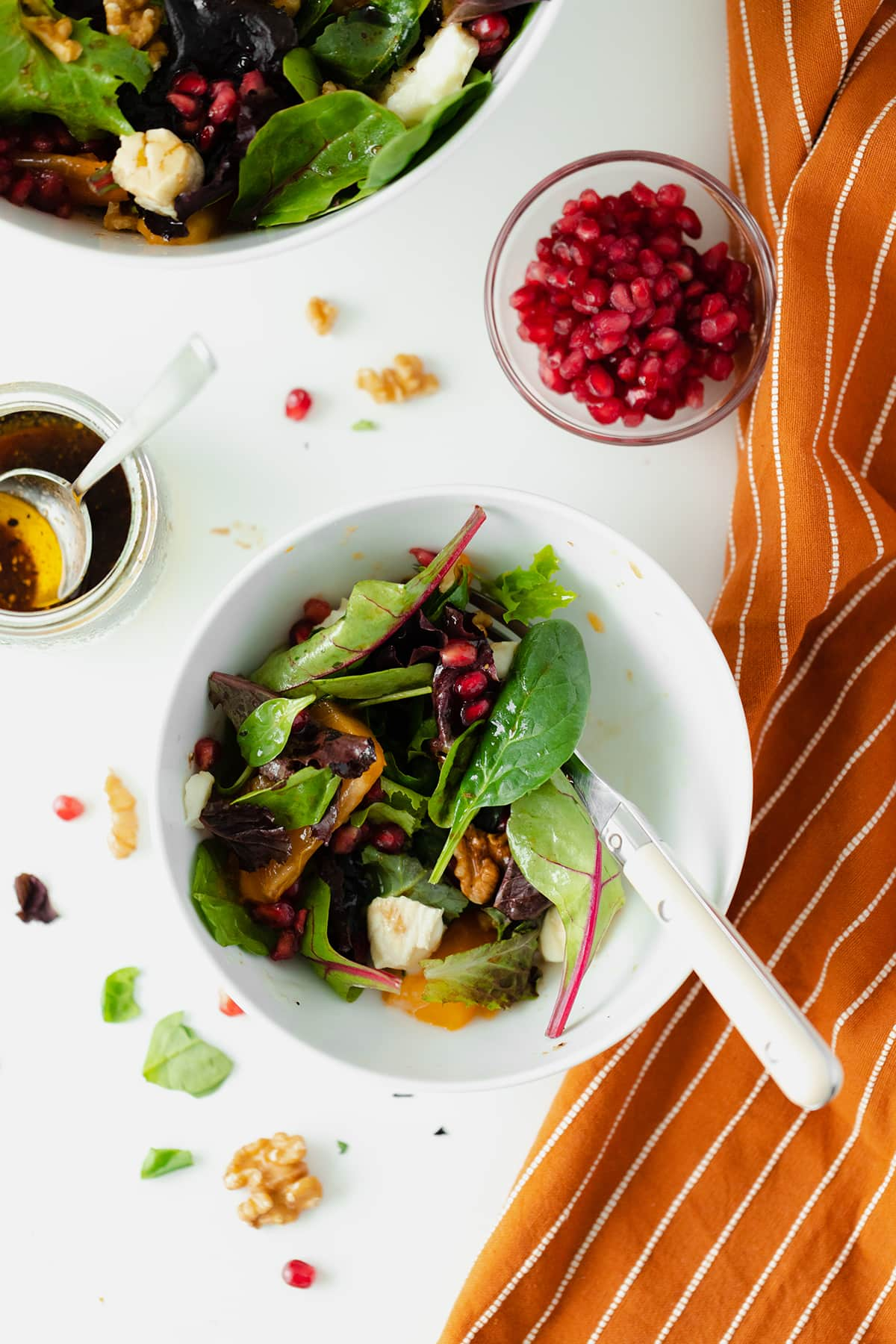 Persimmon Salad with Goat Brie and Pomegranate seeds in a white bowl on a white background with an orange napkin on the right side
