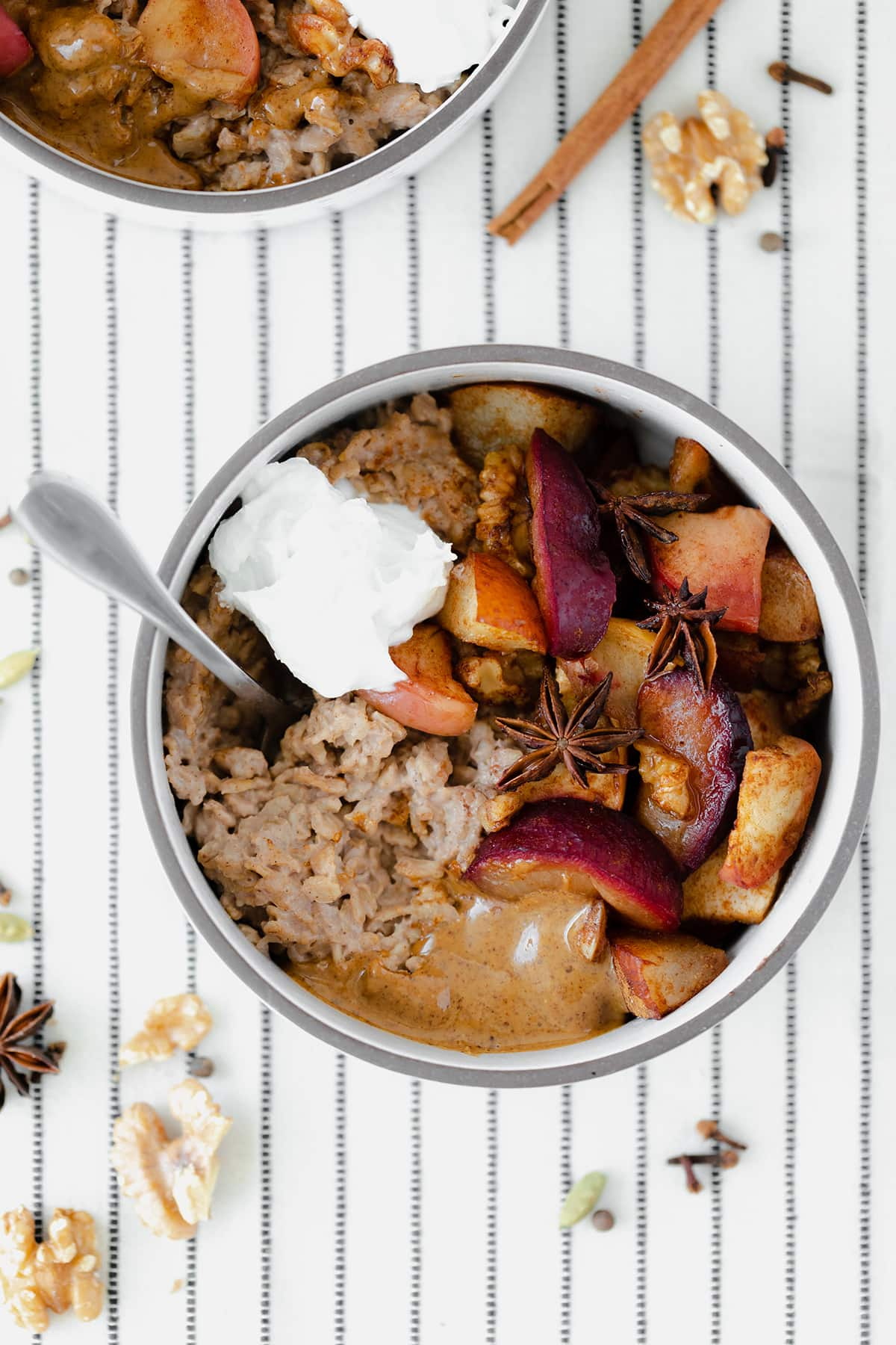 Winter Spiced Oatmeal with Roasted Fruit on a white tablecloth with black stripes.