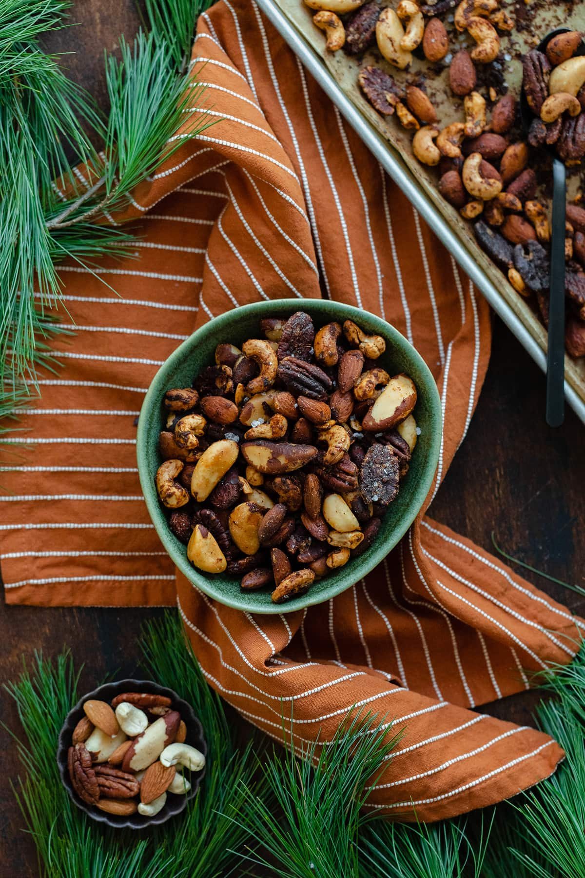Mixed roasted nuts in a green bowl on an orange and white striped napkin. Pine needles peeking into the shot in the top left, bottom left, and bottom right corners. Baking sheet with more nuts in the top right corner.