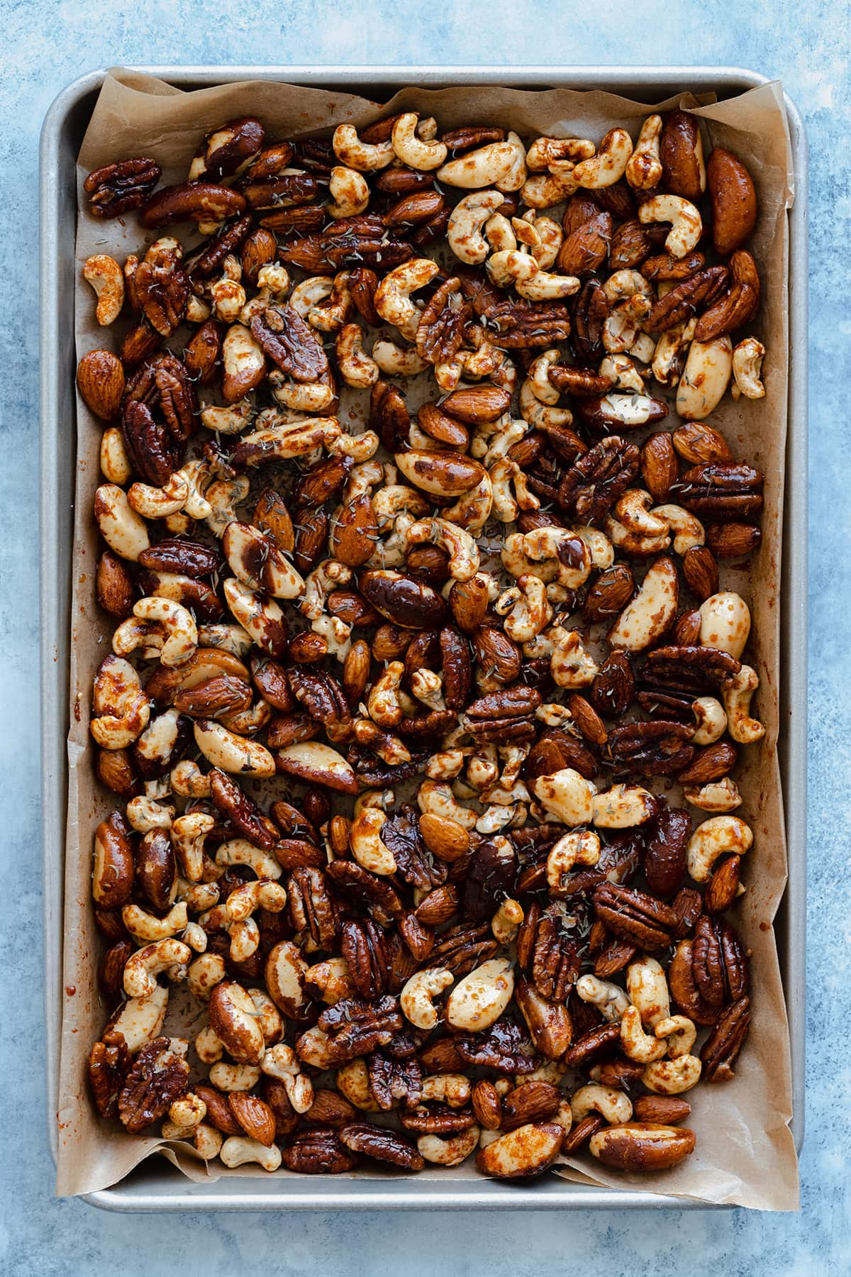 Raw nuts tossed in oil, maple syrup, and cajun spice on a baking sheet lined with baking paper.