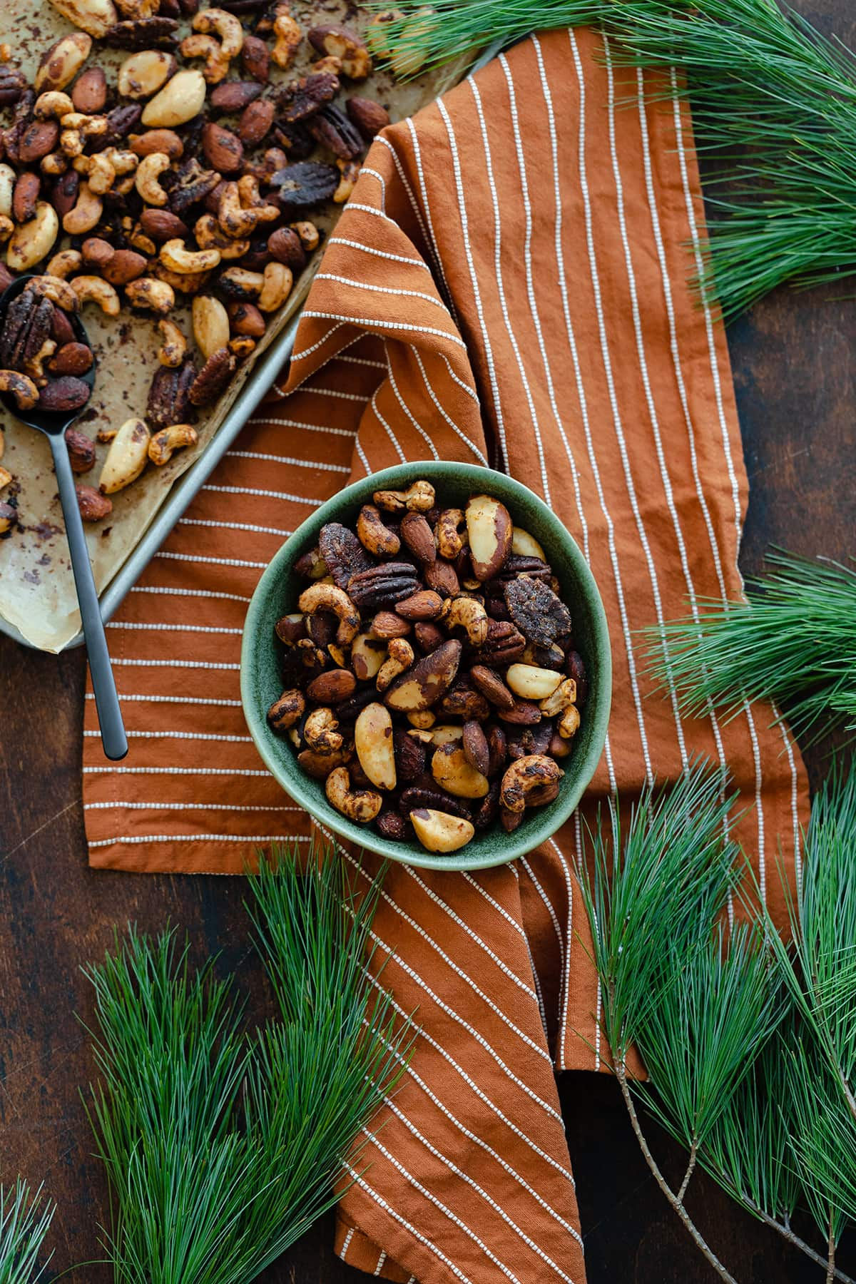 Mixed roasted nuts in a green bowl on an orange and white striped napkin. Pine needles peeking into the shot in the top right, bottom left, and bottom right corners.