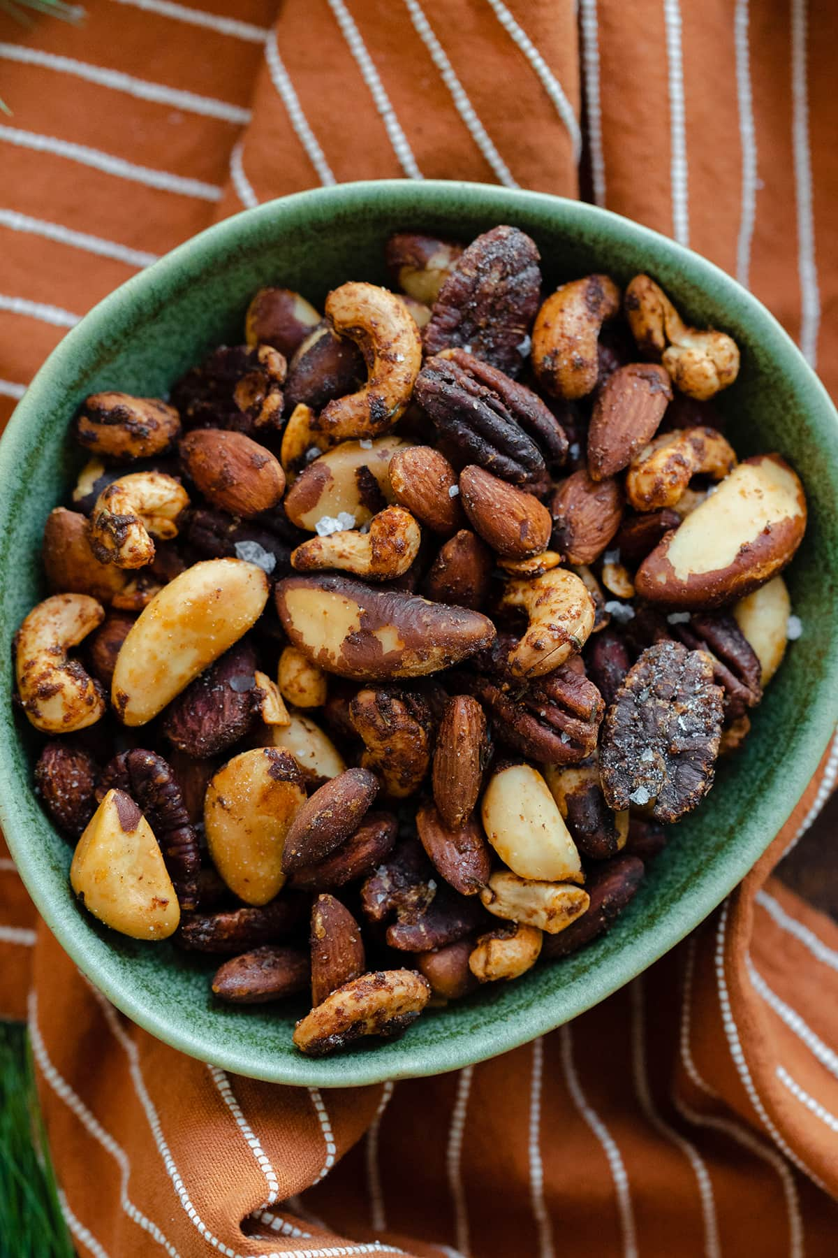 A close-up shot of roasted nuts in a green bowl on an orange and white striped napkin.