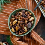 Mixed roasted nuts in a green bowl on an orange and white striped napkin. Pine needles peeking into the shot in the top left and bottom left corner.