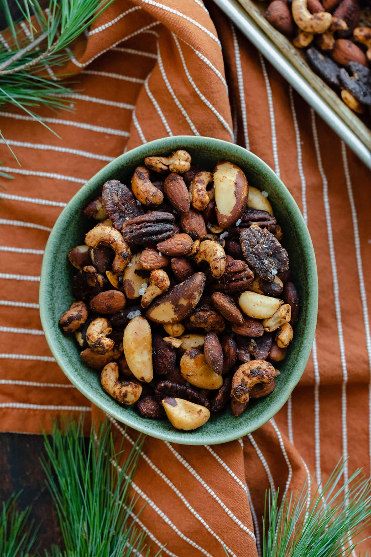 Mixed roasted nuts in a green bowl on an orange and white striped napkin. Pine needles peeking into the shot in the top left, bottom left, and bottom right corners.