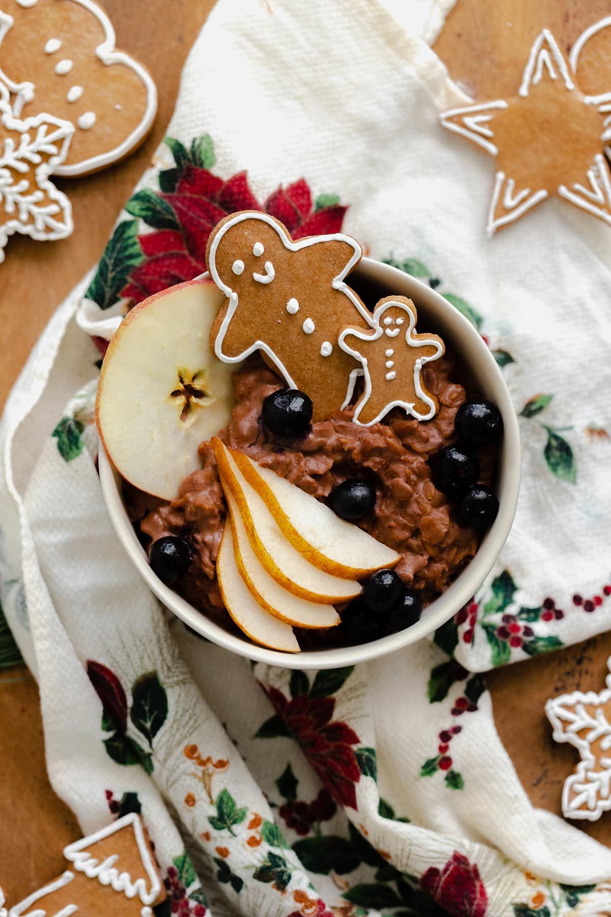 An overhead photo of Gingerbread oatmeal in a beige bowl garnished with sliced pear, a slice of apple, a few blueberries, and two gingrbread men. On light wooden background with a christmas tea towel under the bowl and gingerbread cookies around it.