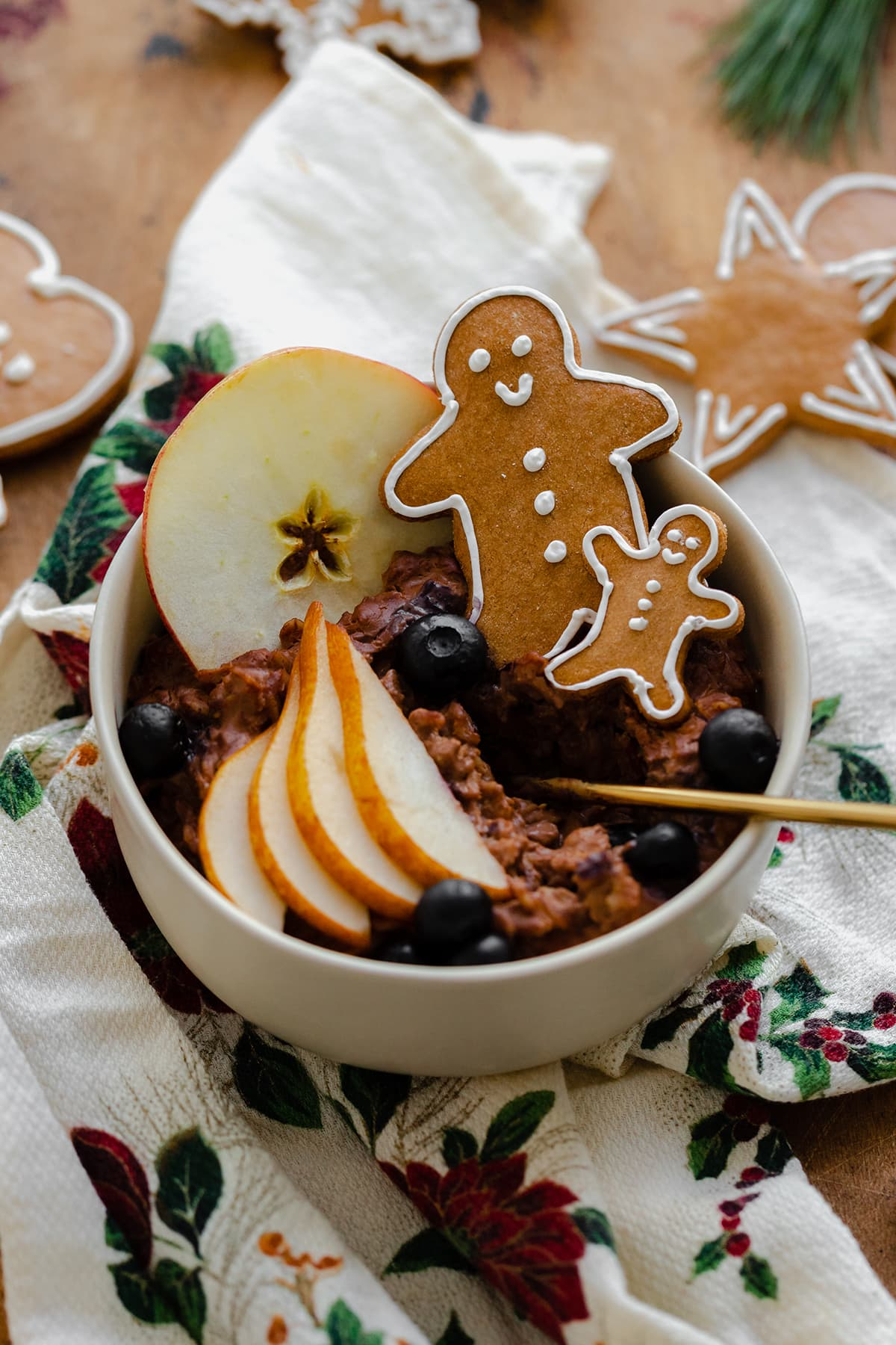 An overhead close up shot of Gingerbread oatmeal in a beige bowl garnished with sliced pear, a slice of apple, a few blueberries, and two gingrbread men. On light wooden background with a christmas tea towel under the bowl and gingerbread cookies around it.