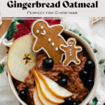 Gingerbread oatmeal with the title in the shot. In a beige bowl garnished with sliced pear, a slice of apple, a few blueberries, and two gingrbread men. On light wooden background with a Christmas tea towel under the bowl.