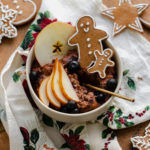 A square shot of Gingerbread oatmeal in a beige bowl garnished with sliced pear, a slice of apple, a few blueberries, and two gingrbread men. On light wooden background with a christmas tea towel under the bowl and gingerbread cookies around it.