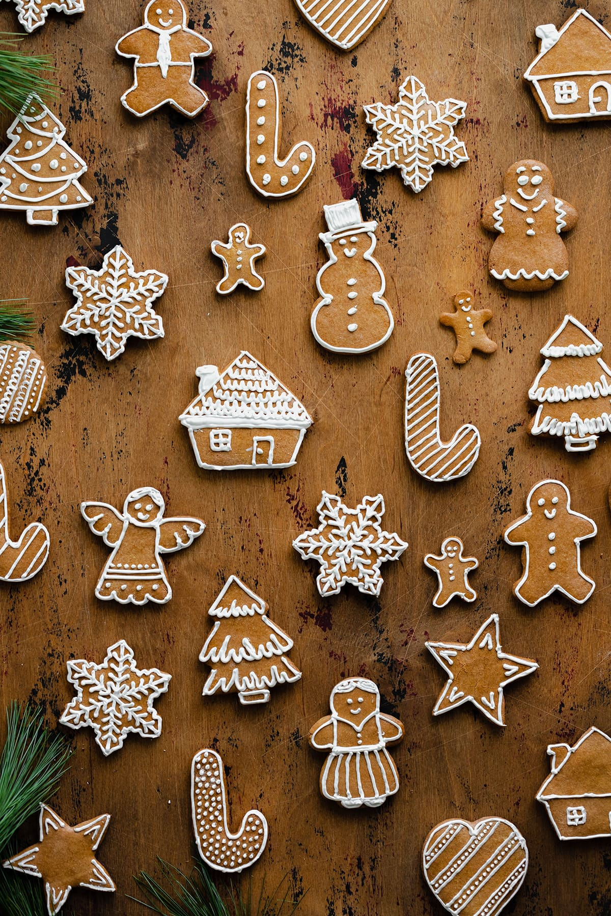 Czech Gingerbread cookies layed out evenly on a light wooden background. Decorated with white icing.