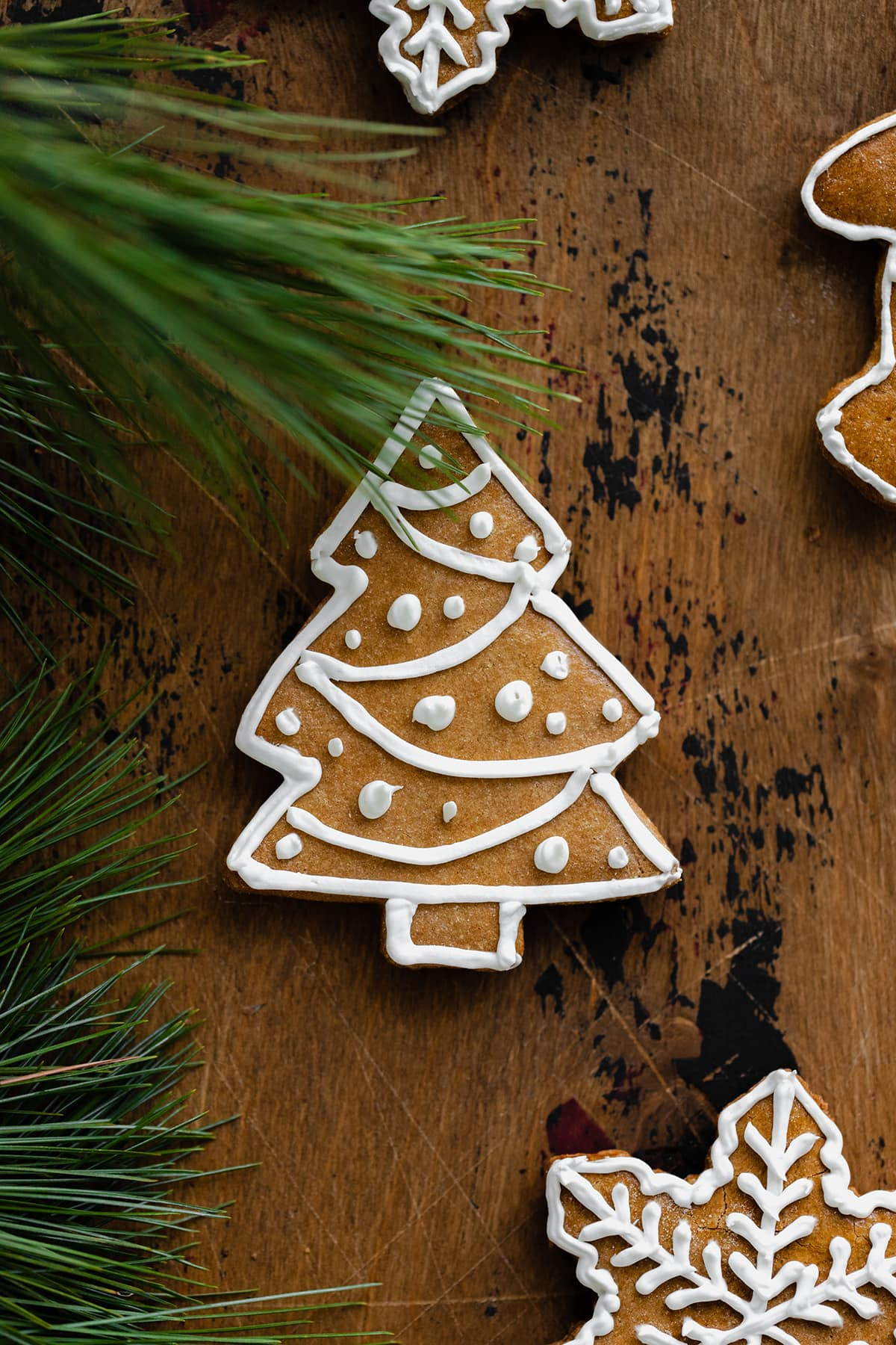 A close up of a Christmas tree shaped gingerbread cookie on a light wooden background. Decorated with white icing.